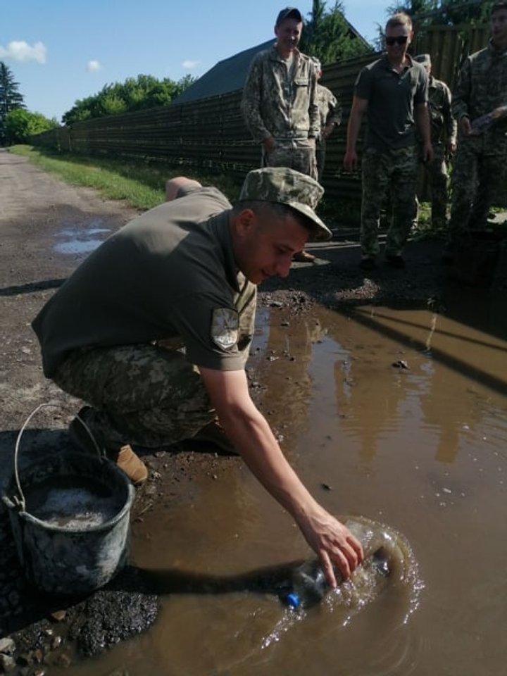 Військовий креатив: на Волині  до приїзду Зеленського військові пляшками вичерпували воду з калюж, - фото
